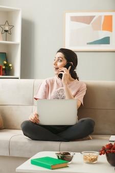 Jeune femme avec ordinateur portable parle au téléphone assise sur un canapé derrière une table basse dans le salon