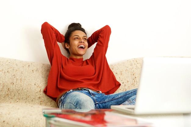 Jeune femme, à, ordinateur portable, rire, chez soi