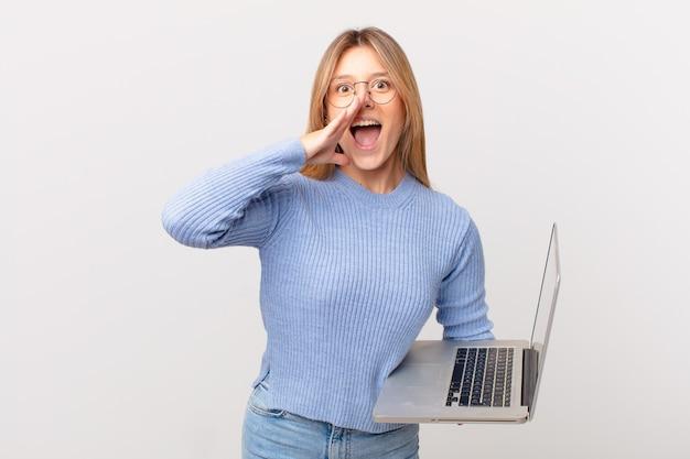 Jeune femme avec un ordinateur portable se sentant heureuse, donnant un grand cri avec les mains à côté de la bouche