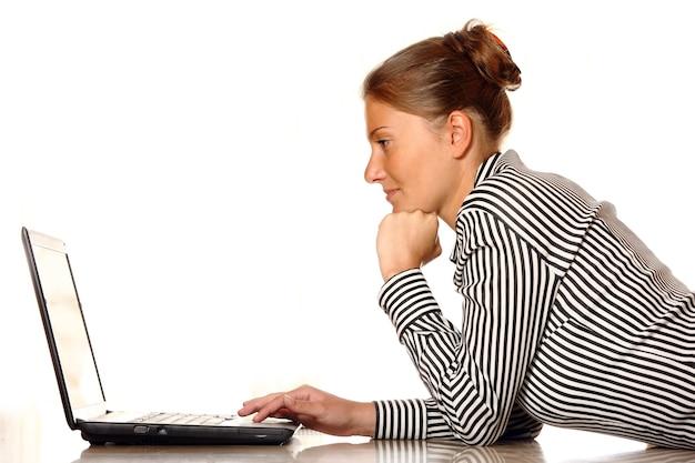 Jeune femme avec ordinateur portable sur le sol