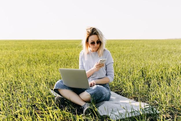 Jeune femme avec un ordinateur portable travaillant, assis dans un champ avec de l'herbe verte fraîche.