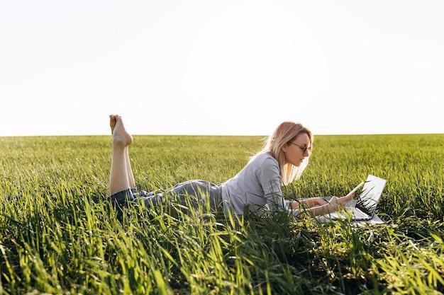 Jeune femme avec un ordinateur portable travaillant, couché dans le champ avec de l'herbe verte fraîche.