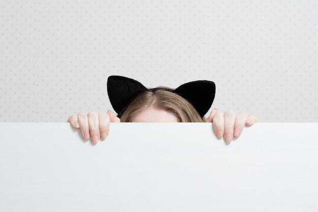 Jeune femme avec des oreilles de chats sur la tête se cache derrière une bannière blanche