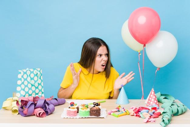 Jeune femme organisant un anniversaire crie fort, garde les yeux ouverts et les mains tendues