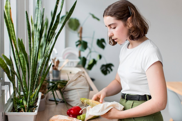 Jeune femme organisant des légumes biologiques dans la cuisine