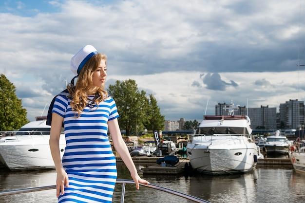 Jeune femme d'origine ethnique caucasienne dans une robe courte à rayures bleues et une casquette sur un yacht posant sur une journée ensoleillée concept de divertissement de l'eau