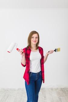 Jeune femme avec des outils de peinture en regardant la caméra