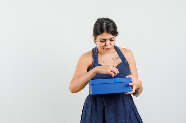 Jeune femme ouvrant une boîte présente en robe et semblant curieuse