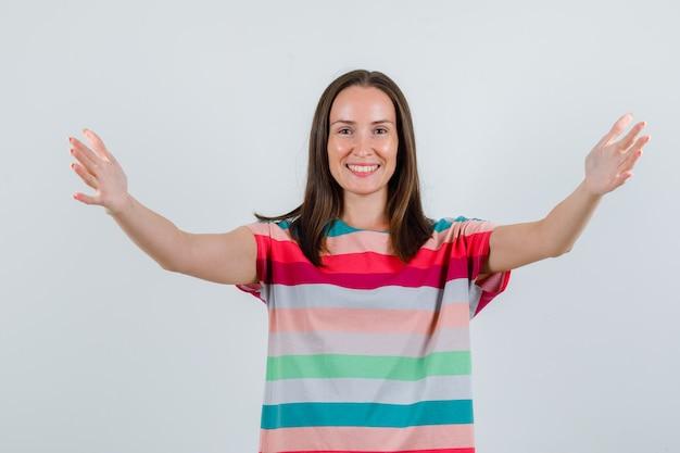 Jeune femme ouvrant les bras larges en t-shirt et à la joyeuse vue de face.