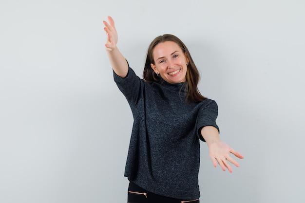 Jeune femme ouvrant les bras pour câlin en chemise et à la bonne humeur