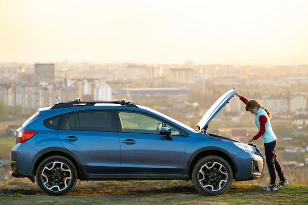 Jeune femme ouvrant le capot d'une voiture en panne ayant des problèmes avec son véhicule. conducteur debout près de l'automobile avec capot sauté.