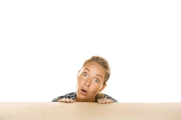 Jeune femme ouvrant le plus gros colis postal sur blanc
