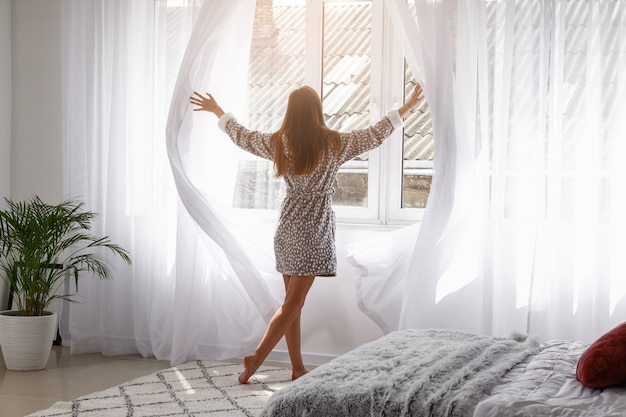 Jeune femme ouvrant des rideaux lumineux dans la chambre à la maison
