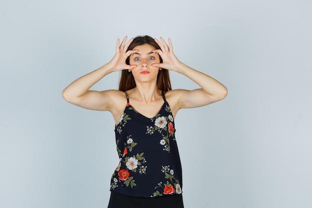 Jeune femme ouvrant les yeux avec les doigts en blouse, jupe et l'air choqué, vue de face.