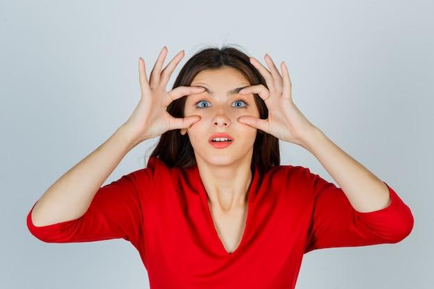 Jeune femme ouvrant les yeux pour voir clairement en chemisier rouge et à la jolie