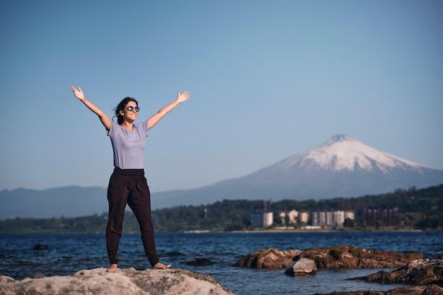 Jeune femme ouvre ses bras en souriant dans un beau paysage avec un lac et des montagnes enneigées