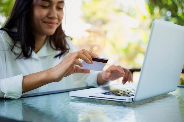 Jeune femme avec paiement par carte de crédit du magasinage en ligne