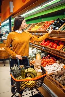 Jeune femme avec panier en épicerie