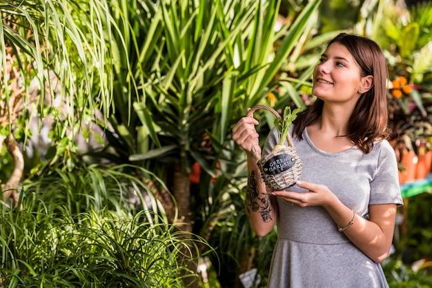 Jeune femme avec panier en regardant les plantes vertes