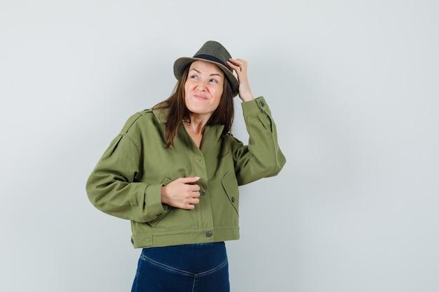 Jeune femme en pantalon veste chapeau se gratter la tête et à oublier