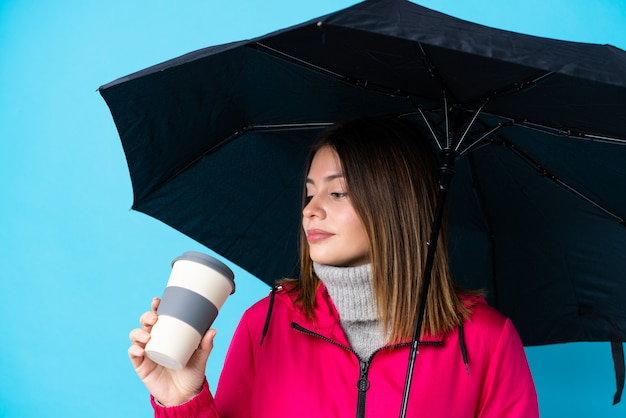Jeune femme avec un parapluie et café à emporter sur un mur bleu isolé