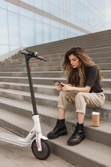 Jeune femme parcourant son téléphone mobile