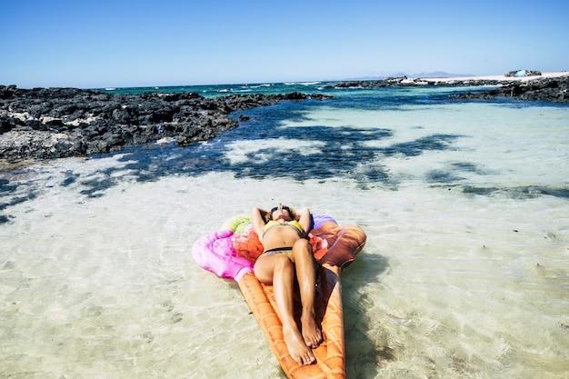 Jeune femme parfaite au corps magnifique s'amuser et se détendre sur un matelas lilo tendance coloré dans une plage paradisiaque tropicale des caraïbes et de l'eau de mer transparente