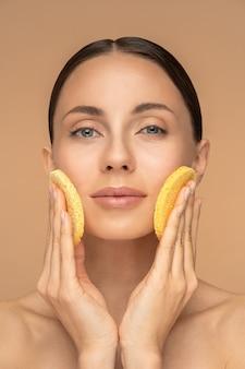Jeune femme parfaite avec un maquillage nude et des épaules nues nettoyant son visage avec une éponge exfoliante