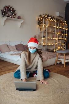 Jeune femme parlant avec un ami en ligne sur un ordinateur portable pendant la célébration de noël à la maison