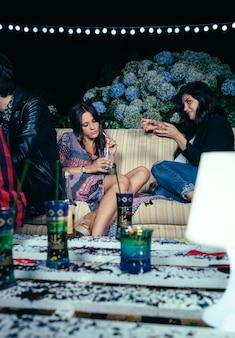 Jeune femme parlant avec une amie assise sur un canapé lors d'une fête en plein air. concept d'amitié et de célébrations.