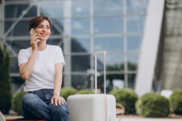Jeune femme parlant au téléphone à l'aéroport