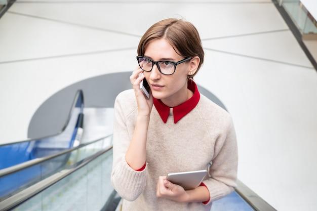 Jeune femme parlant au téléphone à un escalier mécanique. femme d'affaires sur un escalier mobile à l'aide de la technologie moderne