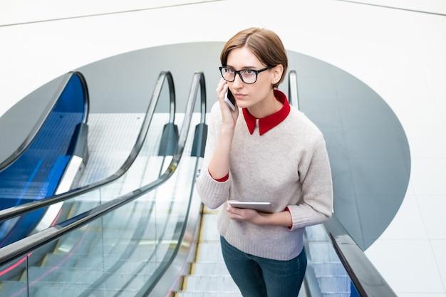 Jeune femme parlant au téléphone à l'escalier en mouvement. femme d'affaires sur un escalier roulant à l'aide de la technologie moderne