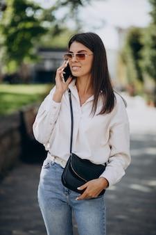 Jeune femme parlant au téléphone à l'extérieur de la rue