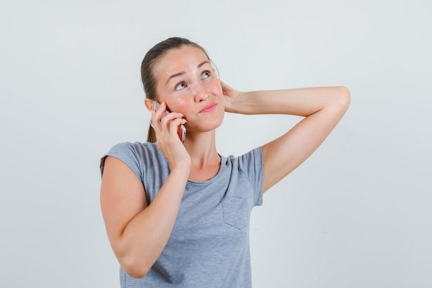 Jeune femme parlant au téléphone mobile en t-shirt gris et à la vue de face, hésitante.