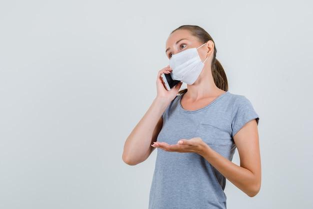 Jeune femme parlant au téléphone portable et demandant quelque chose en t-shirt gris, masque, vue de face.