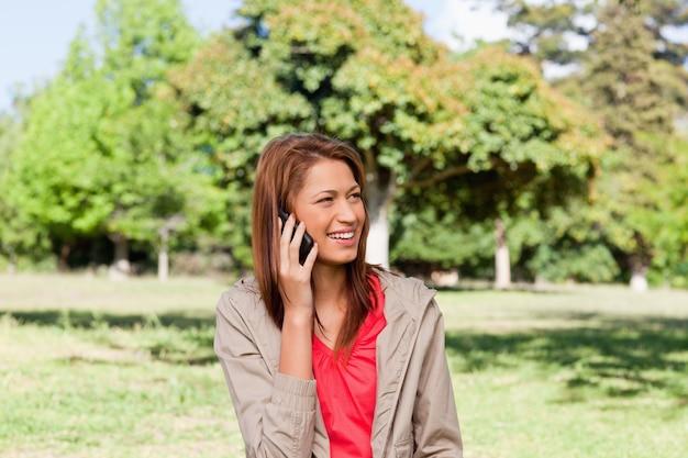 Jeune femme parlant au téléphone tout en regardant vers le côté dans une zone de prairie lumineuse