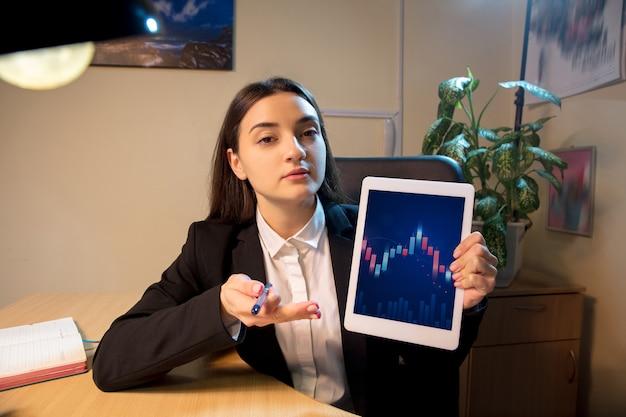 Jeune femme parlant au travail pendant la vidéoconférence avec des collègues au bureau à domicile