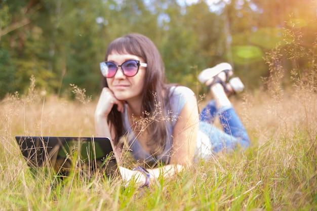 Jeune femme parlant émotionnellement au téléphone devant un ordinateur portable.