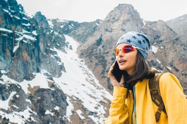 Jeune femme parlant sur smartphone dans les montagnes rocheuses