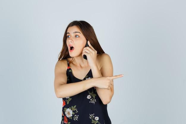 Jeune femme parlant sur smartphone, pointant de côté en blouse et l'air choquée. vue de face.