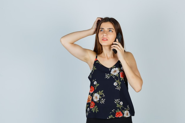 Jeune femme parlant sur smartphone tout en se grattant la tête en blouse et en regardant pensive, vue de face.