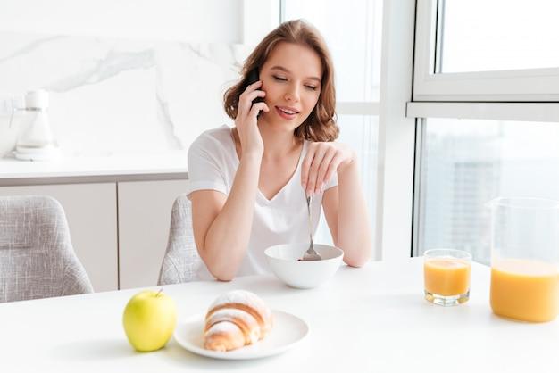 Jeune femme parlant sur téléphone mobile tout en prenant son petit déjeuner à la table de la cuisine