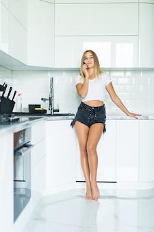 Jeune femme parlant sur téléphone mobile tout en utilisant un ordinateur portable dans la cuisine à la maison