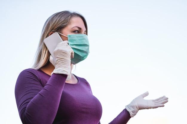 Jeune femme parlant avec un téléphone portable en plein air portant un masque facial et des gants en latex