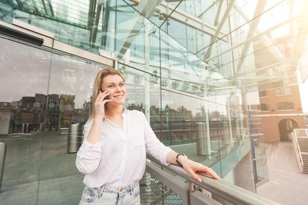 Jeune femme parle au téléphone portable avec un vitrage