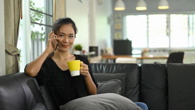 Une jeune femme parle sur un téléphone mobile assis sur un canapé en cuir