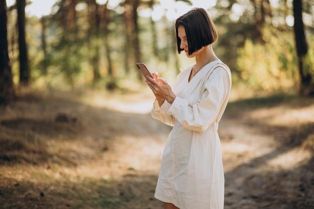 Jeune femme, parler téléphone, dans parc