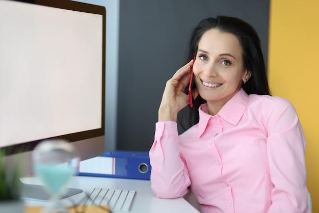 Jeune femme, parler téléphone portable, dans, bureau