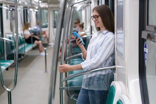 Jeune femme passagère utilisant un téléphone intelligent mobile discutant dans les réseaux sociaux dans une rame de métro au métro